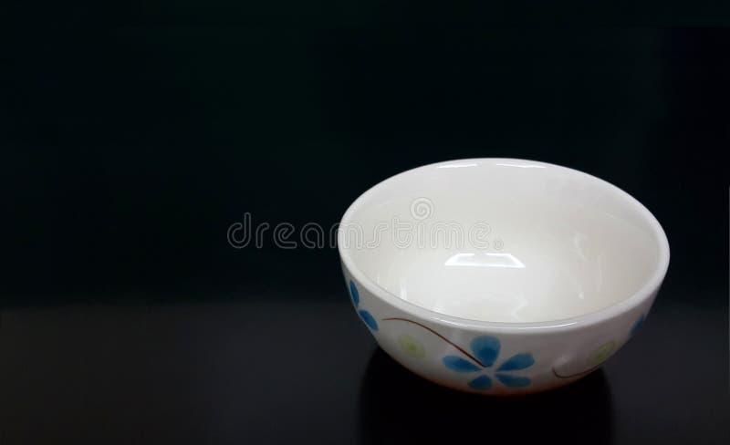 在黑背景的空的白色碗 库存图片