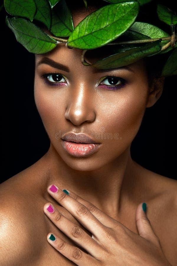 在黑背景的美丽的妇女画象 摆在与绿色叶子的年轻非洲的女孩 华美组成 库存图片