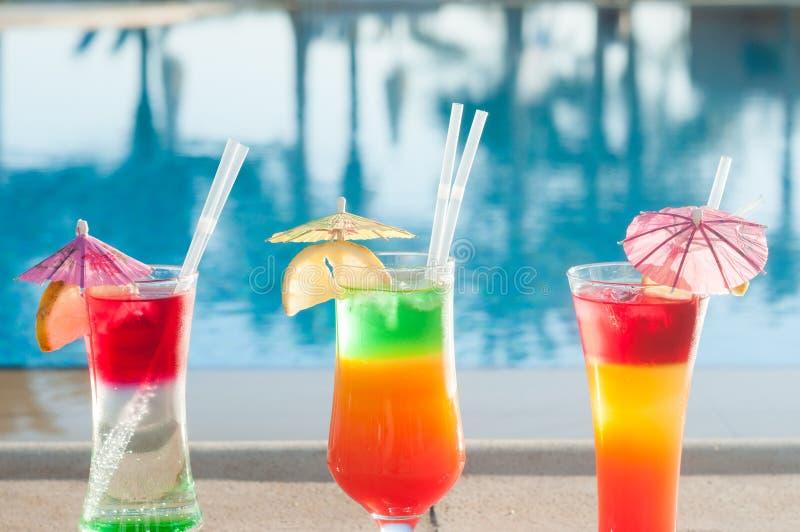 在水背景的色的鸡尾酒  在水池附近的五颜六色的鸡尾酒 海滩党 夏天饮料 库存图片