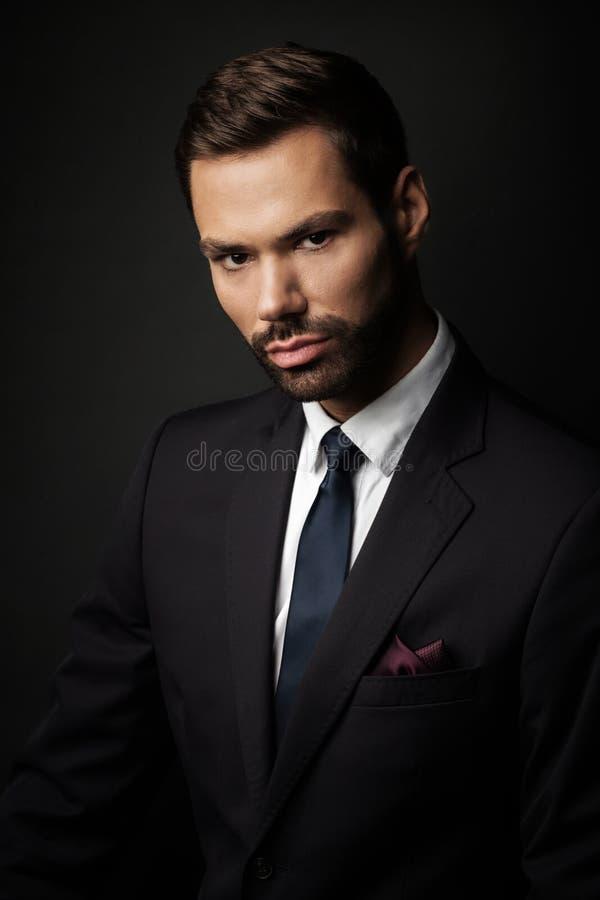 在黑背景的英俊的年轻商人画象 免版税图库摄影