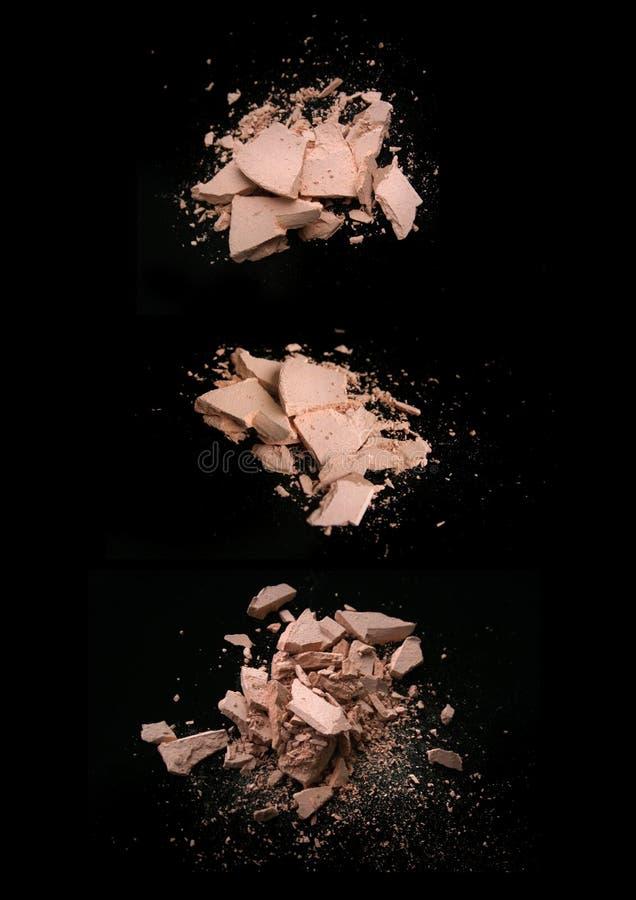 在黑背景的被击碎的紧凑粉末 免版税库存图片