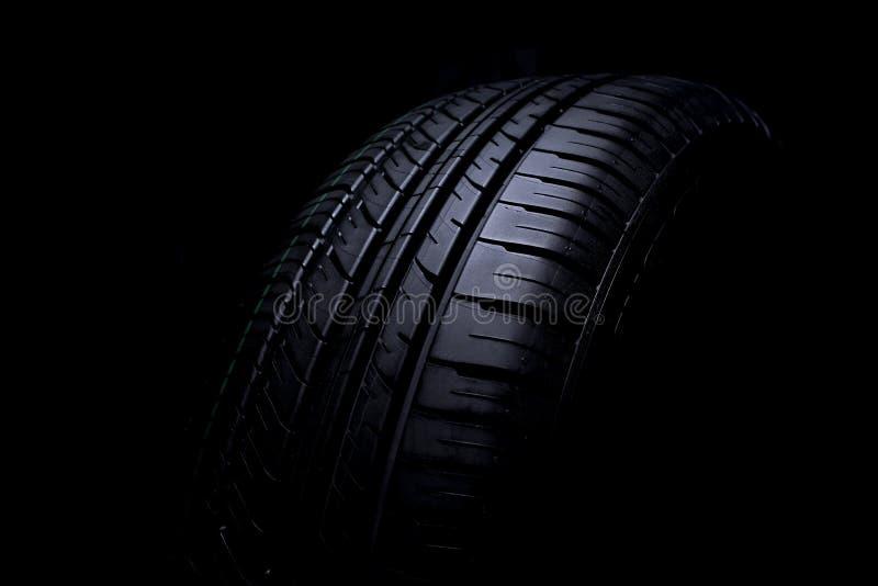在黑背景的轮胎汽车 库存图片