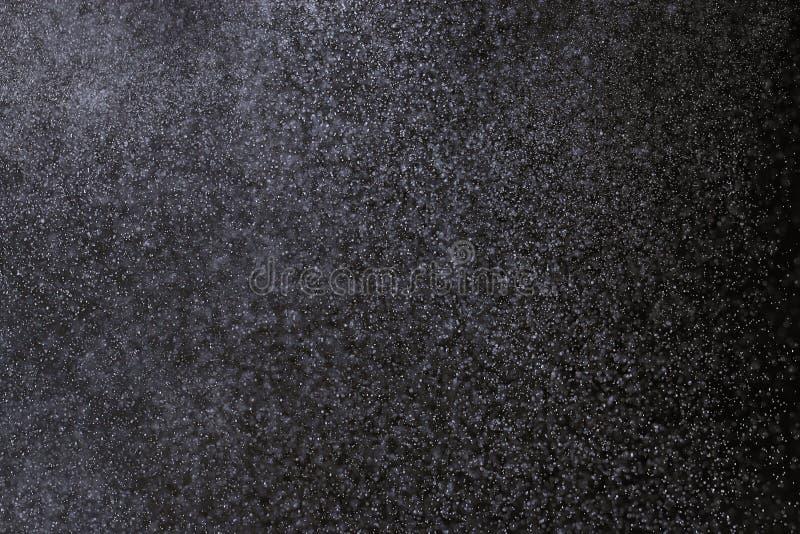 在黑背景的雪雨 免版税库存图片