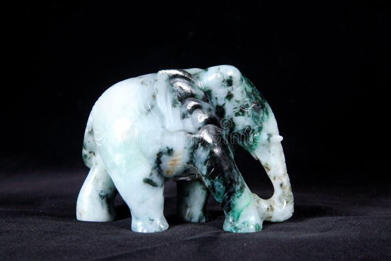 在黑背景隔绝的大象玉雕塑 库存图片