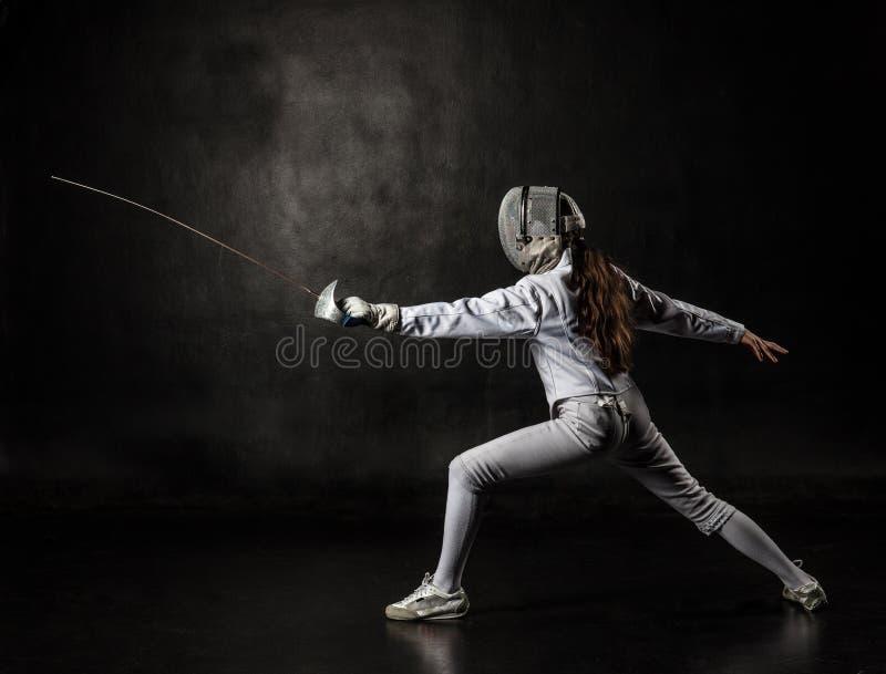 在黑背景隔绝的女性击剑者 图库摄影