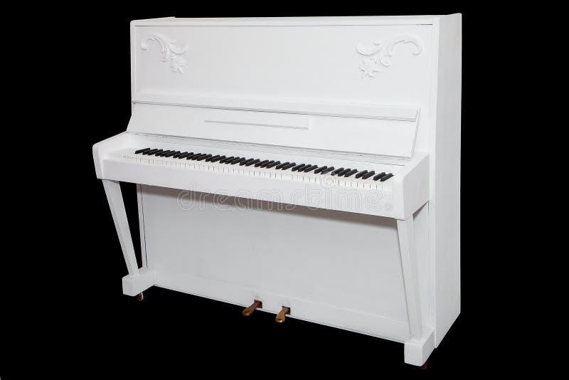 在黑背景隔绝的白色钢琴 库存照片