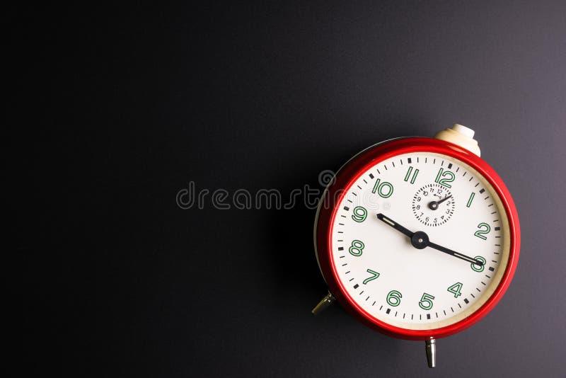 在黑背景,时间概念,仓促的红色闹钟 库存图片