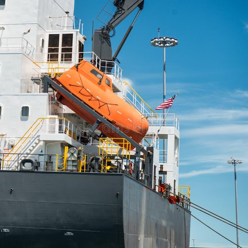 在货船安装的紧急乘员组撤离的橙色自由下落救生船 库存照片