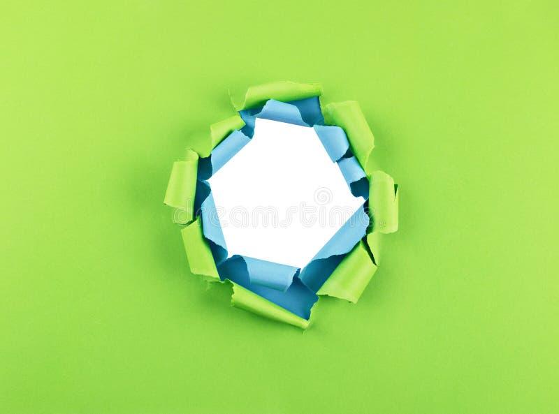 在绿色和蓝纸的孔 免版税库存照片