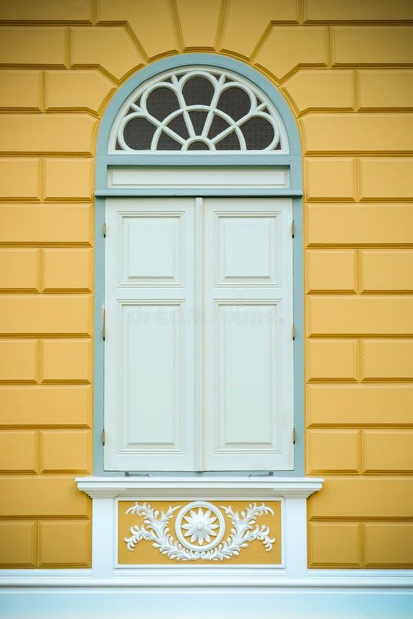 在黄色墙壁上的白色木窗口古董样式 免版税库存图片