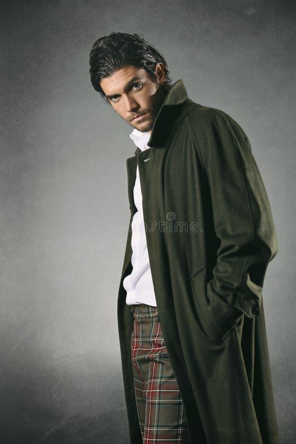 在绿色外套和纹理背景的男性时装模特儿 免版税库存图片