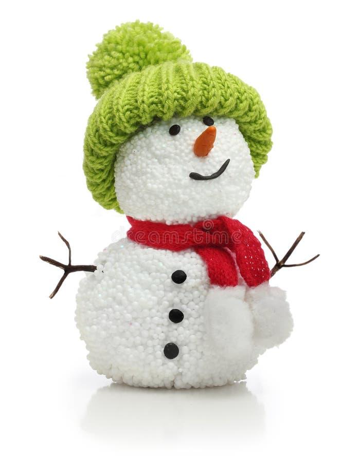 在绿色帽子和红色围巾的雪人 库存图片