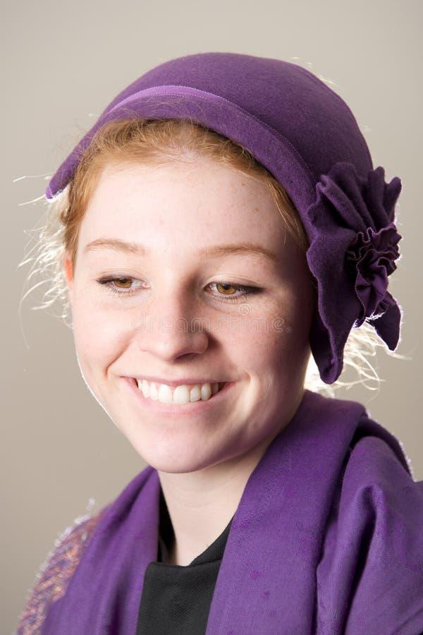 在紫色帽子尖酸的嘴唇的微笑的红头发人 免版税库存照片