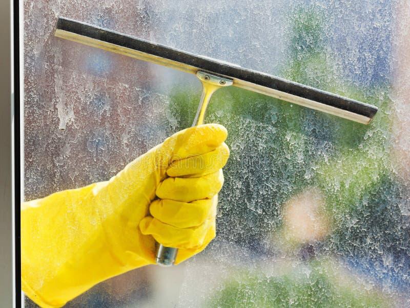 在黄色手套的手由橡皮刮板洗涤窗口 免版税库存图片