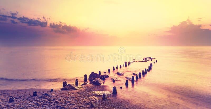 在紫色日落以后,平安的海风景 库存图片