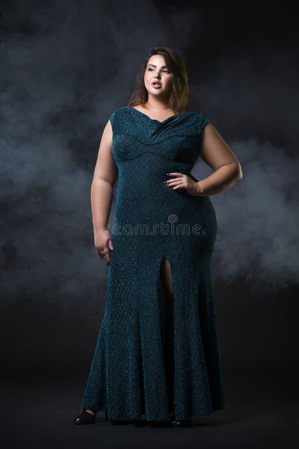 在绿色晚礼服,黑背景的肥胖妇女,超重女性身体的正大小时装模特儿 免版税图库摄影