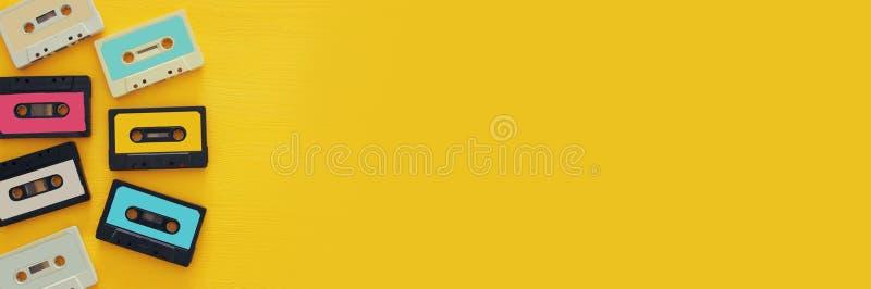 在黄色木桌的减速火箭的盒式磁带收藏 顶视图 复制空间 免版税库存照片