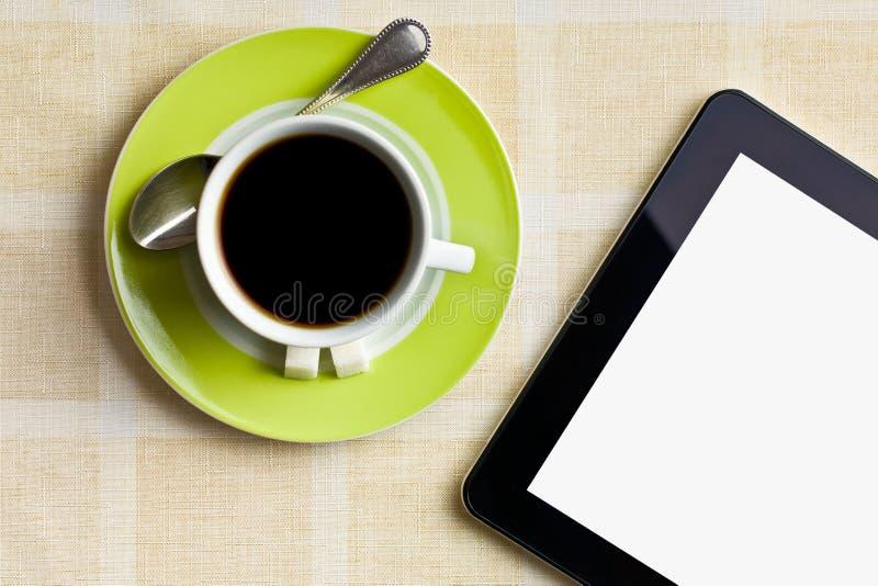 在绿色杯子的无奶咖啡有计算机片剂的 免版税库存照片