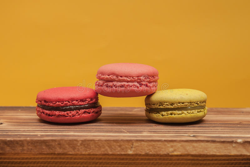 在黄色柔和的淡色彩堆积的堆五颜六色的macarons被隔绝 库存图片