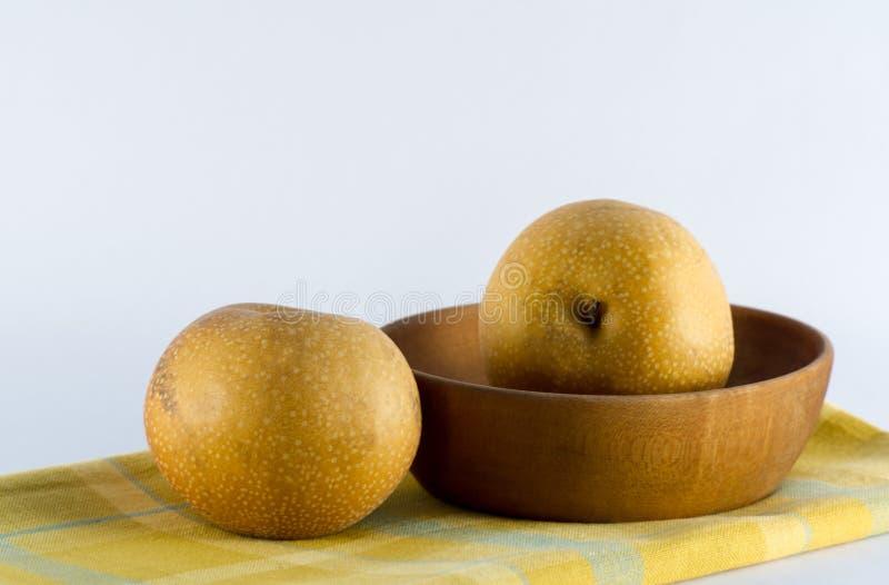 在黄色格子花呢披肩餐巾木头碗的亚洲梨 库存照片