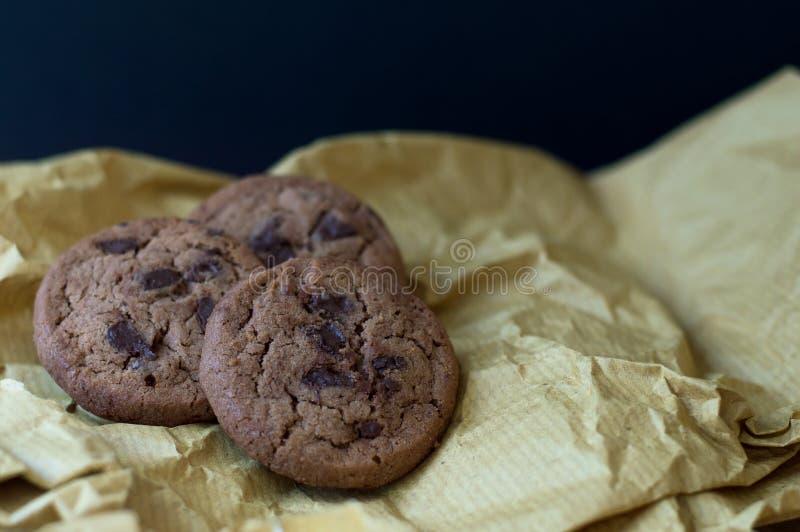 在黄色牛皮纸的三个巧克力曲奇饼 库存图片