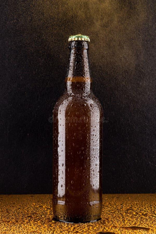 在黑色的冷的棕色啤酒瓶 库存照片
