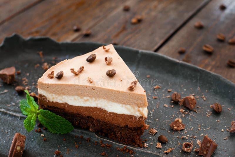 在黑色的盘子的层状蛋白牛奶酥蛋糕到木头里 免版税库存照片
