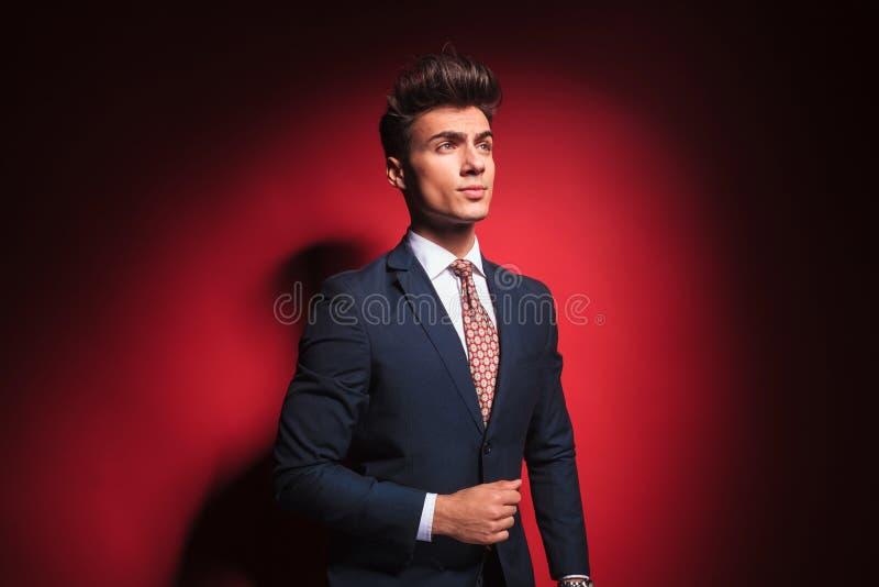 在黑色的年轻商人与安排他的夹克的红色领带 图库摄影