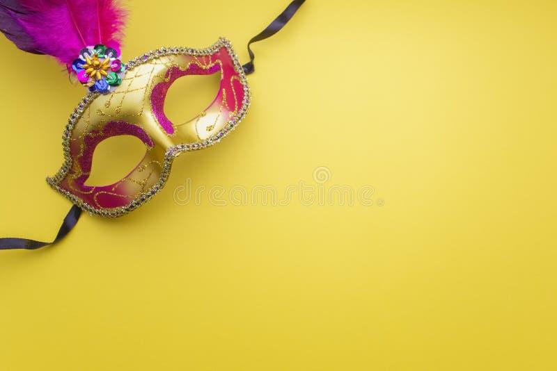 在黄色背景的五颜六色的狂欢节或carnivale面具 屏蔽威尼斯式 顶视图 免版税库存图片