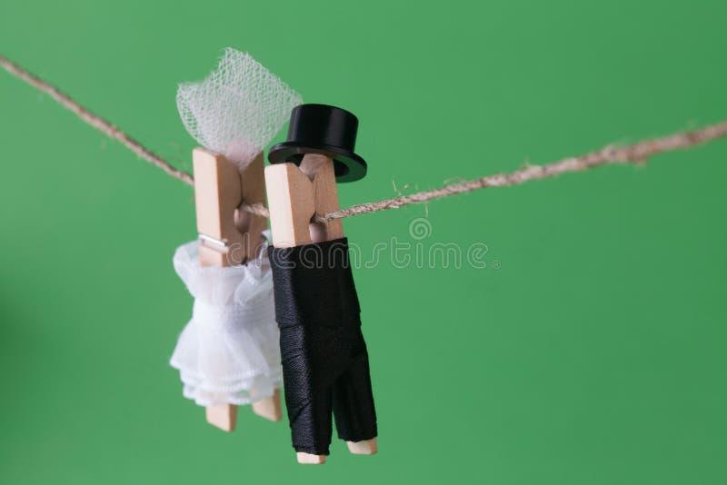 在绿色背景的晒衣夹字符 白色礼服和新郎字符人衣服帽子的新娘 爱概念照片 免版税库存图片
