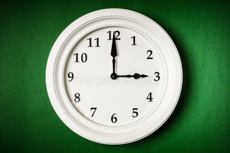 在绿色背景的白色时钟 库存图片
