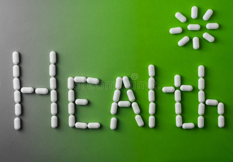 在绿色背景的词健康 白色片剂,一种健康生活方式的概念 免版税库存图片