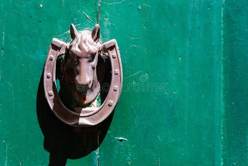 在绿色背景的马敲门人 库存照片