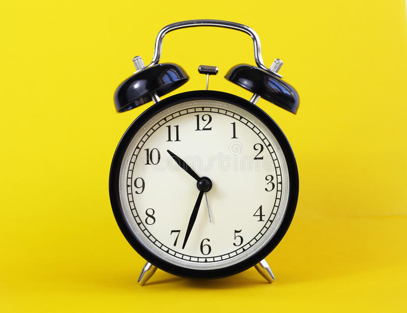 在黄色背景的经典台式时钟 图库摄影