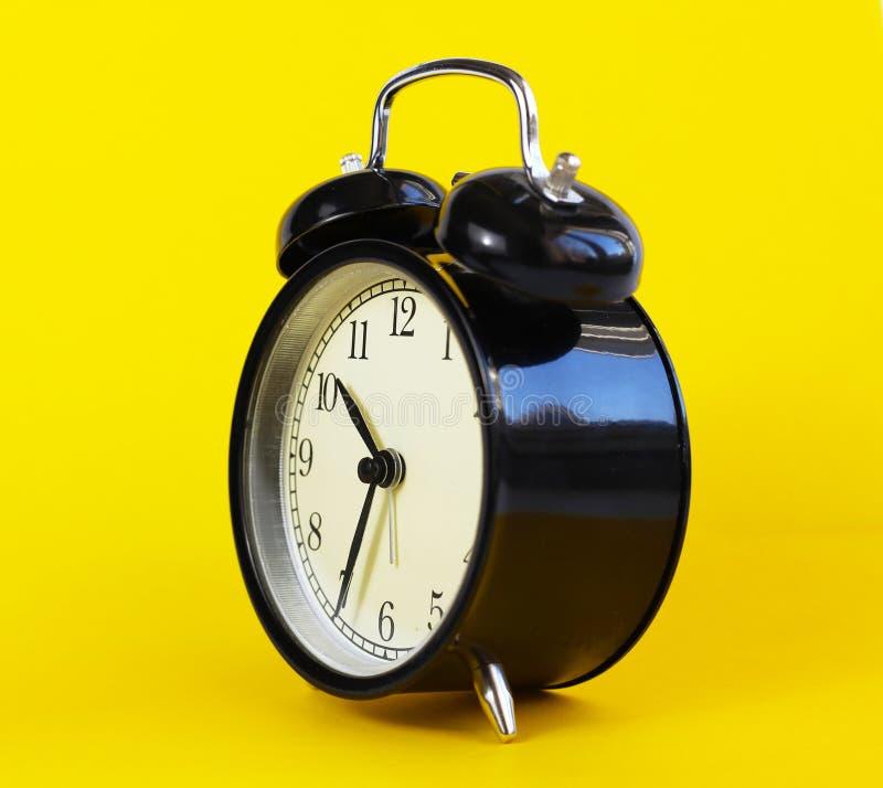 在黄色背景的经典台式时钟 免版税库存图片
