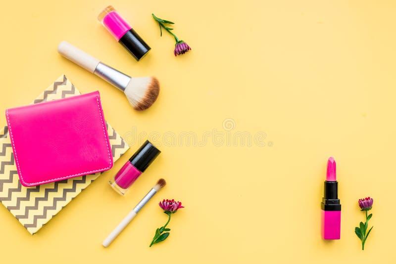 在黄色背景顶视图的装饰化妆用品 免版税库存照片