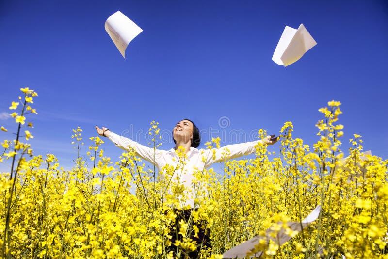 在黄色花中的年轻女实业家投掷纸自由 库存图片