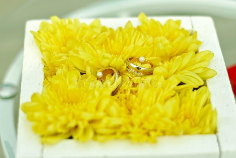 在黄色花的婚戒 免版税库存图片