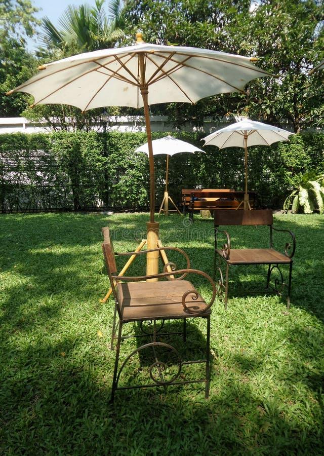 在绿色草坪的庭院椅子在白色伞下 库存照片