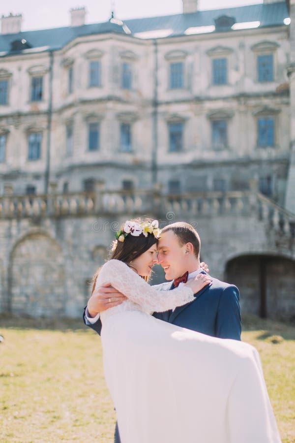 在绿色草坪的有吸引力的新婚佳偶对在美丽的被破坏的巴洛克式的宫殿附近 拿着他的爱恋的新郎迷人的新娘 库存图片