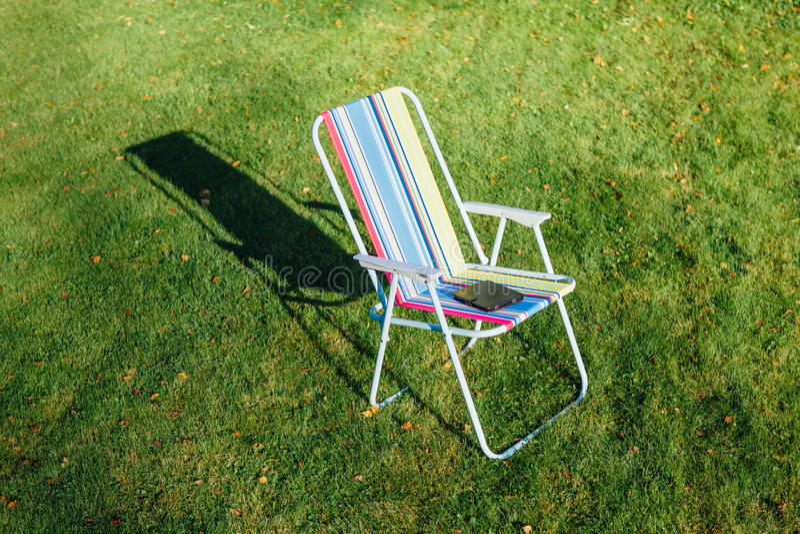 在绿色草坪背景的庭院椅子 免版税图库摄影