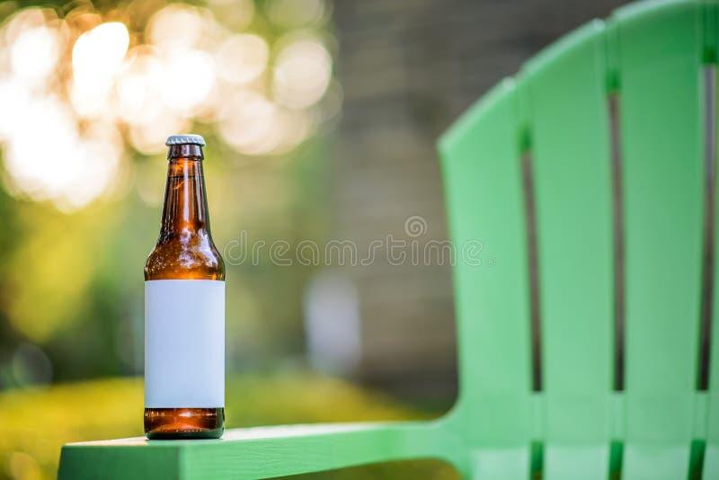 在绿色草椅的空白的标签啤酒瓶 库存图片