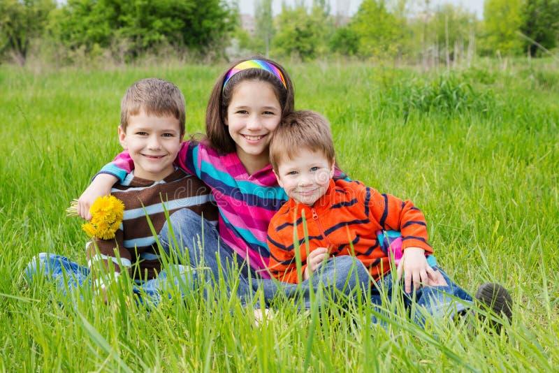 在绿色草甸的三个微笑的孩子 图库摄影