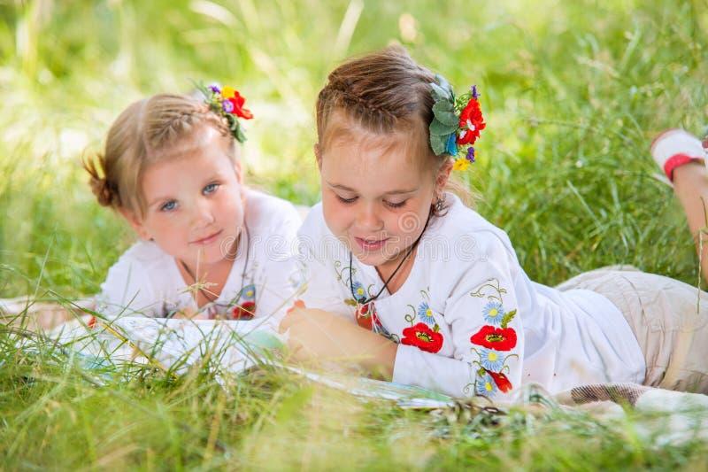 在绿色草甸的两本小女孩阅读书 免版税库存图片