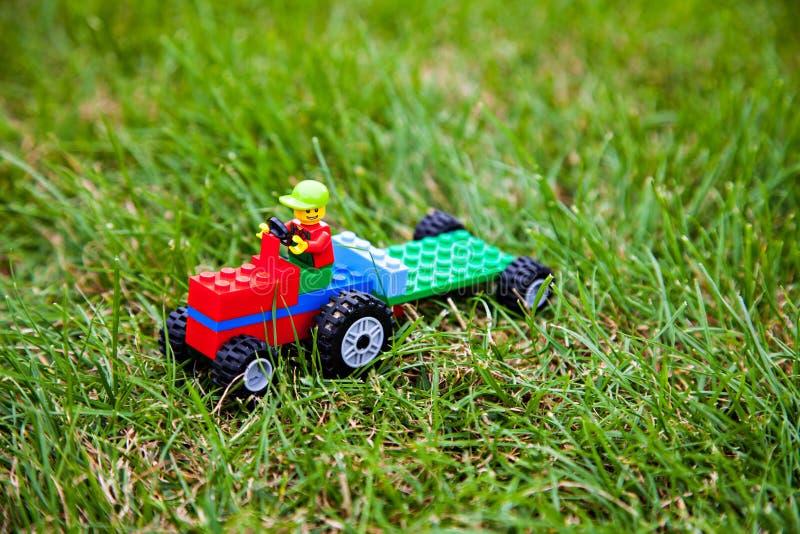 在绿色草甸的玩具lego拖拉机 库存图片