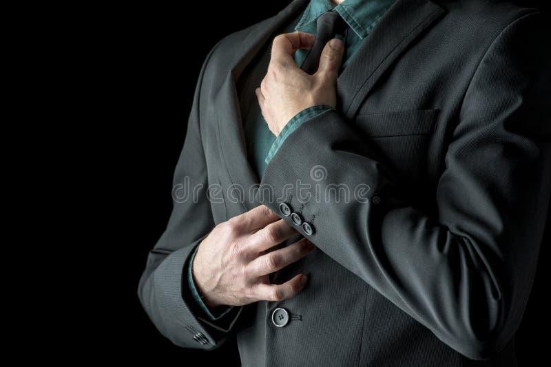 在绿色衬衣的调整他的黑领带的商人和衣服 免版税库存图片