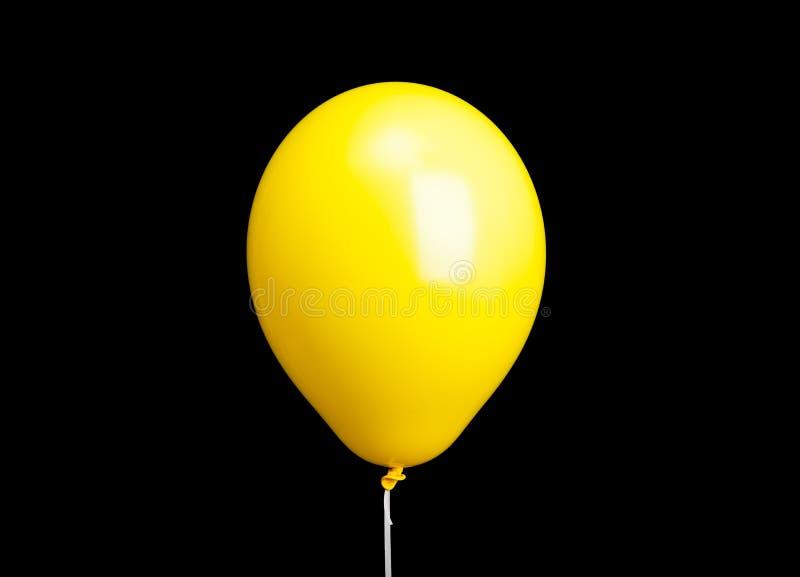 在黑色隔绝的白色丝带的黄色气球 库存照片