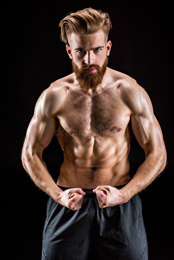 在黑色隔绝的赤裸上身有胡子爱好健美者摆在 免版税库存图片