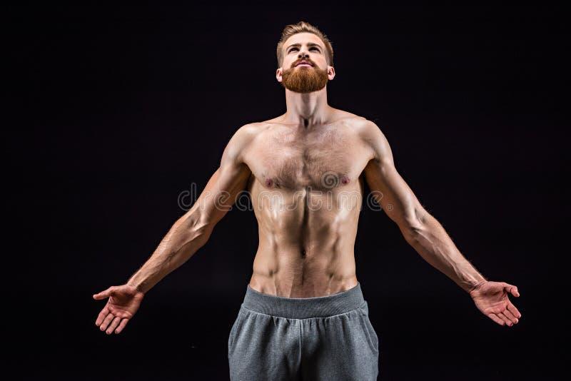 在黑色隔绝的赤裸上身有胡子爱好健美者摆在 库存照片