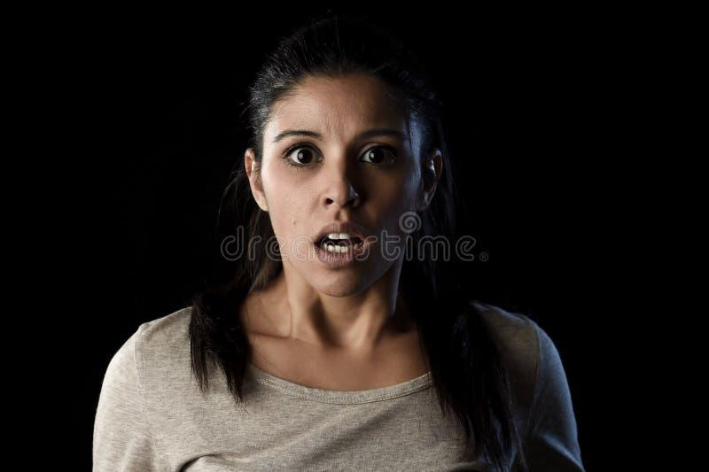 在黑色震动的年轻美丽的害怕的西班牙妇女和惊奇面对表示隔绝的 库存照片